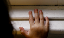 Photo of child's hand on a wall with chipping paint